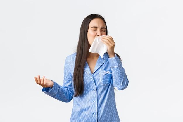 Menina asiática de pijama azul espirrando em um cochilo, tendo alergia sazonal ou passando mal, ficando em casa