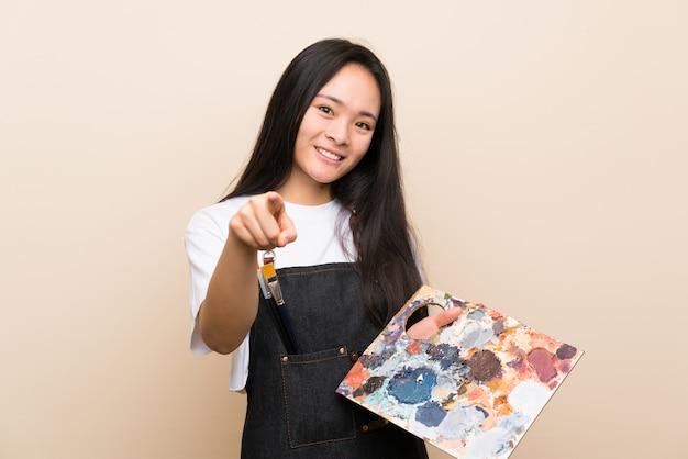 Menina asiática de pintor adolescente aponta o dedo para você com uma expressão confiante