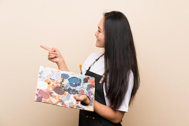 Menina asiática de pintor adolescente, apontando para o lado para apresentar um produto