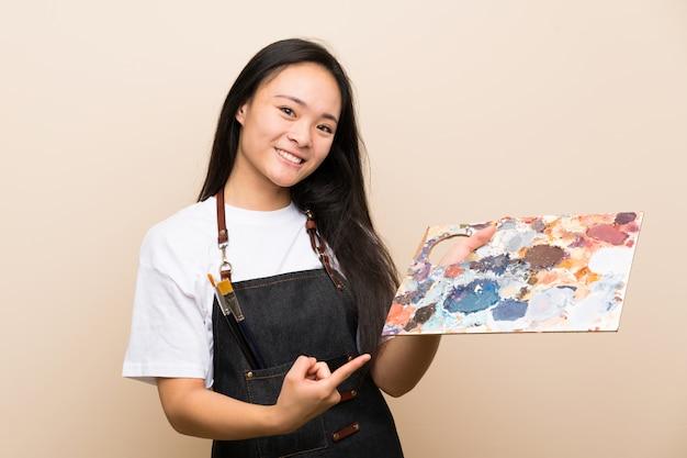 Menina asiática de pintor adolescente e apontando-o
