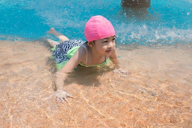 Menina asiática de quatro anos na piscina