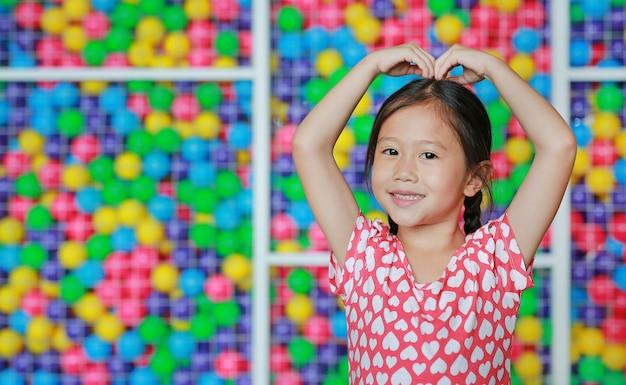 Menina asiática de sorriso que faz o sinal do coração na cabeça