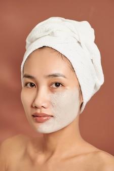 Menina asiática de spa aplicando máscara de argila facial. tratamentos de beleza. sobre fundo azul.