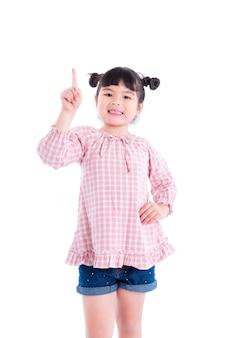 Menina asiática dedo apontando para cima e sorri sobre fundo branco