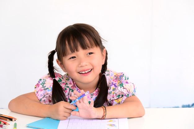 Menina asiática deitada, desenhando ou fazendo lição de casa no livro de papel para crianças pré-escolares na parede branca de casa