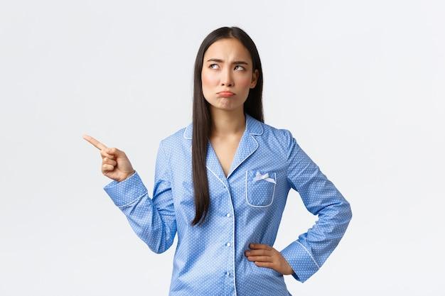 Menina asiática desapontada fazendo beicinho de pijama azul, carrancuda e emburrada apontando olhando o canto superior esquerdo insatisfeita, olhando com antipatia, reclamando de estar de pé, fundo branco