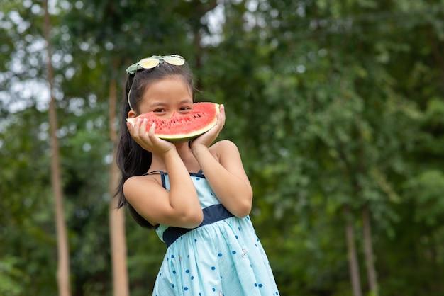 Menina asiática detém melancia
