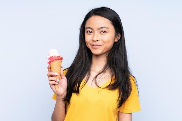 Menina asiática do adolescente com um sorvete de corneta isolado no azul