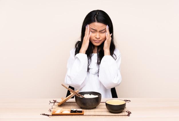 Menina asiática do adolescente que come a comida asiática isolada na parede bege com dor de cabeça