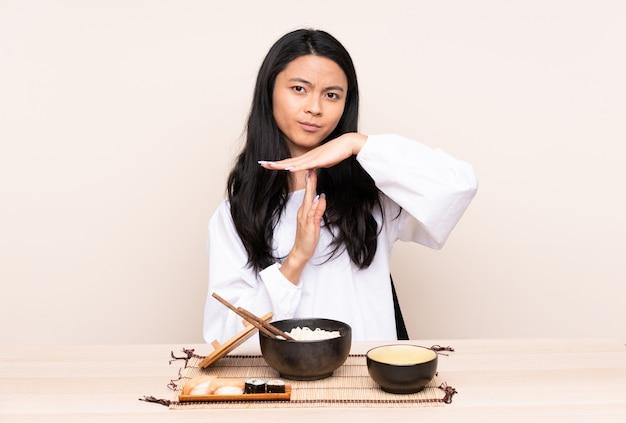 Menina asiática do adolescente que come a comida asiática isolada na parede bege que faz o gesto de intervalo