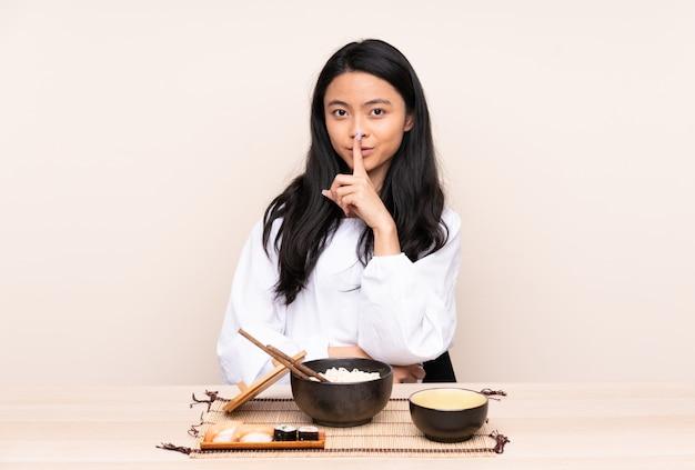 Menina asiática do adolescente que come a comida asiática isolada na parede bege que mostra um sinal do gesto do silêncio que põe o dedo na boca