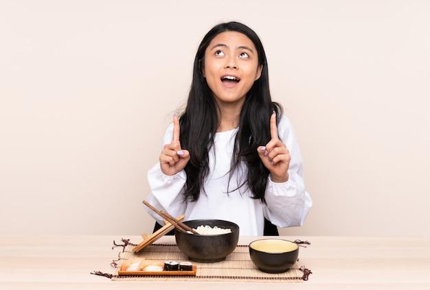 Menina asiática do adolescente que come a comida asiática isolada na parede bege surpreendida e apontando para cima