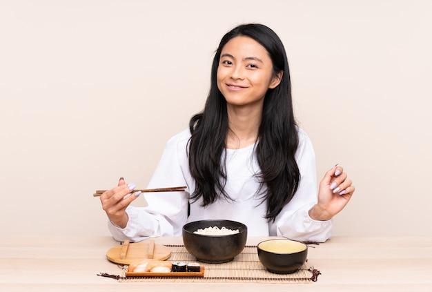 Menina asiática do adolescente que come a comida asiática isolada no bege