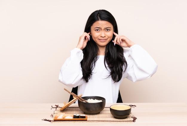 Menina asiática do adolescente que come a comida asiática isolada no fundo bege frustrado e que cobre as orelhas