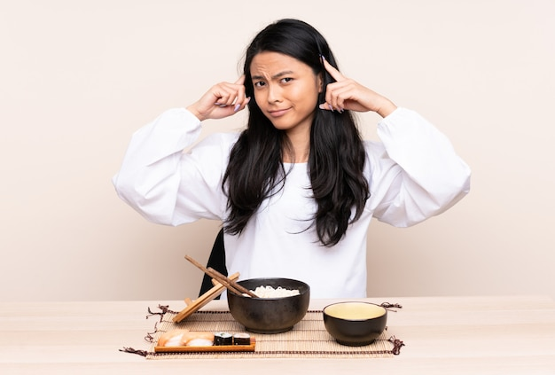 Menina asiática do adolescente que come a comida asiática isolada no fundo bege que tem dúvidas e pensamento