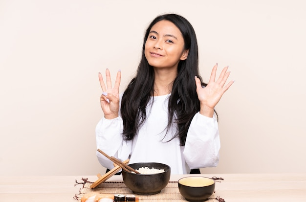 Menina asiática do adolescente que come a comida asiática na parede bege que conta oito com dedos