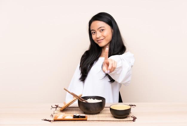 Menina asiática do adolescente que come a comida asiática na parede bege que mostra e que levanta um dedo