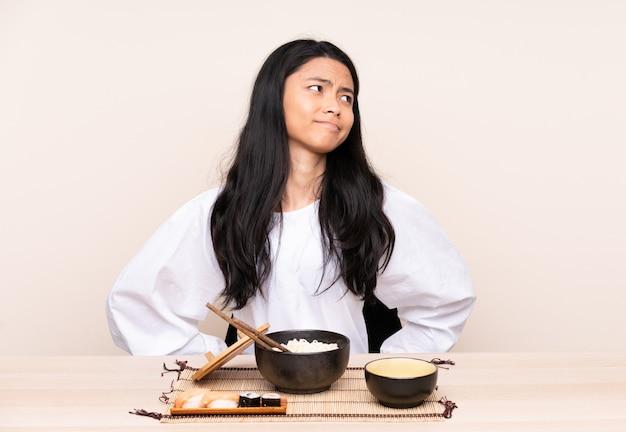 Menina asiática do adolescente que come a comida asiática na parede bege que sofre da dor nas costas por ter feito um esforço