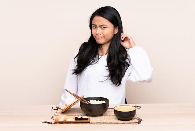 Menina asiática do adolescente que come a comida asiática na parede bege que tem dúvidas