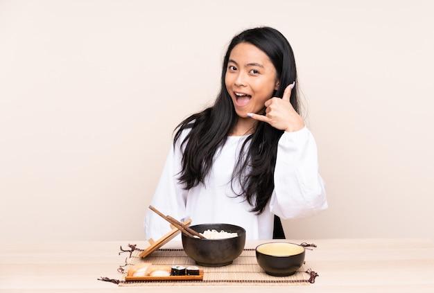 Menina asiática do adolescente que come o alimento asiático isolado no fundo bege que faz o gesto do telefone. ligue para mim de volta