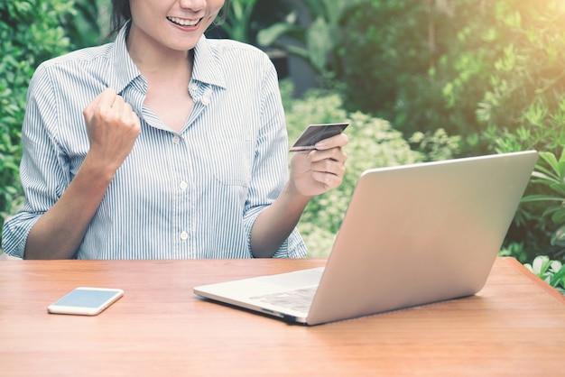 Menina asiática do cliente que compra em linha com um portátil e um cartão de crédito que senta-se no jardim em casa.