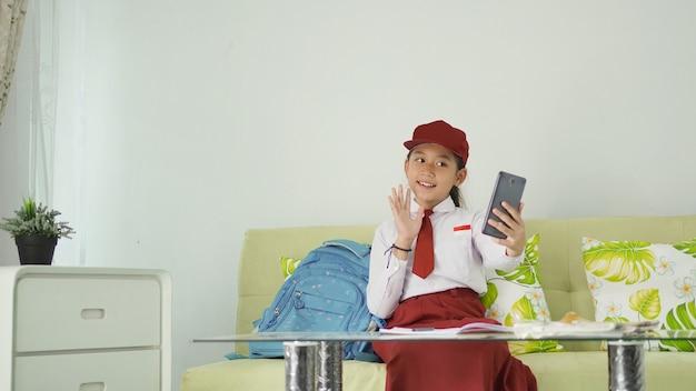 Menina asiática do ensino fundamental cumprimentando a tela do telefone em casa e estudando