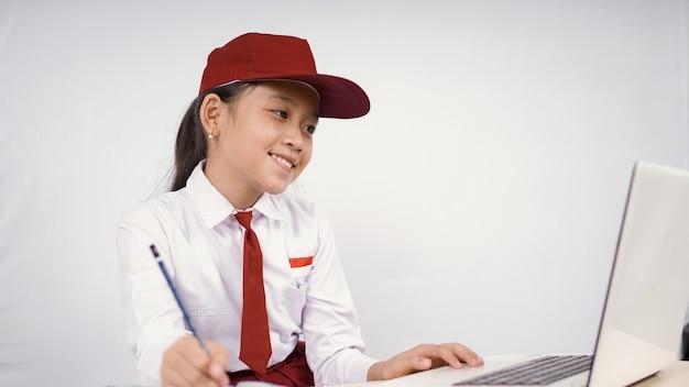 Menina asiática do ensino fundamental escrevendo a ideia da tela do laptop isolada no fundo branco