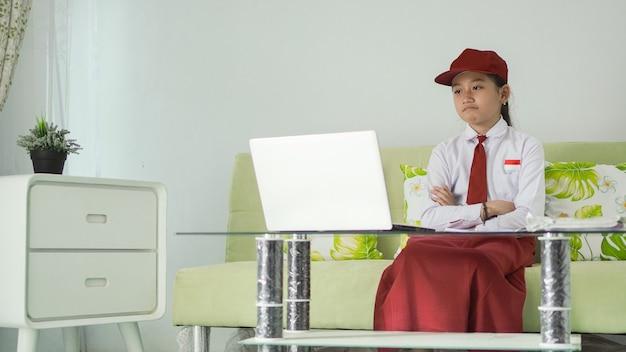 Menina asiática do ensino fundamental estudando em casa e olhando para a tela do laptop irritada