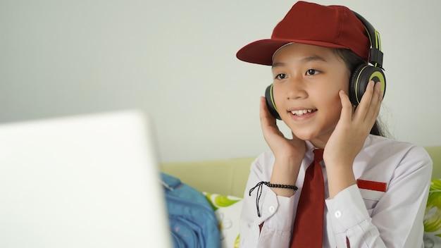 Menina asiática do ensino fundamental estudando online e ouvindo atentamente em casa
