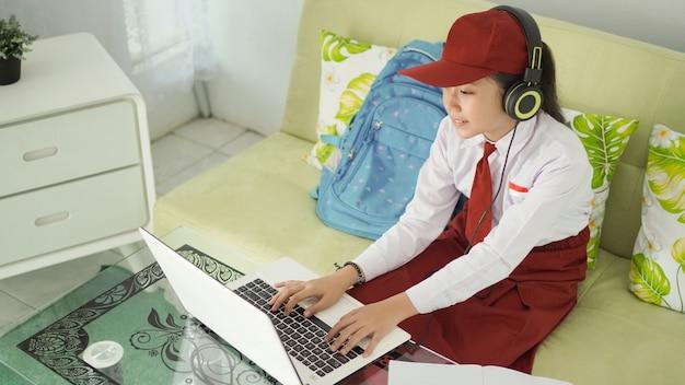 Menina asiática do ensino fundamental estudando online em casa digitando enquanto ouve