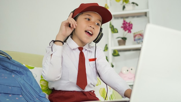 Menina asiática do ensino fundamental on-line estudando apaixonadamente em casa