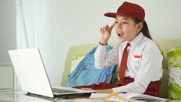 Menina asiática do ensino fundamental que estuda online em casa tem uma ideia brilhante na tela do laptop