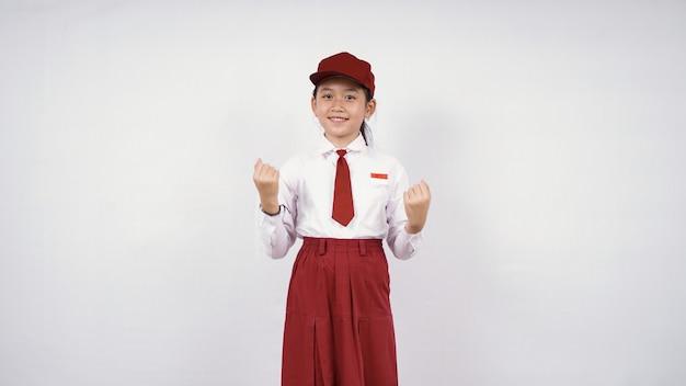 Menina asiática do ensino fundamental se sentindo bem-sucedida isolada no fundo branco