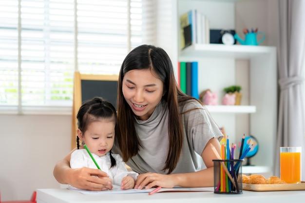 Menina asiática do estudante do jardim de infância com imagem da pintura da mãe no livro com lápis da cor em casa, homeschooling e ensino à distância.