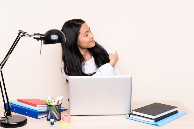 Menina asiática do estudante em um local de trabalho com um laptop isolado no bege