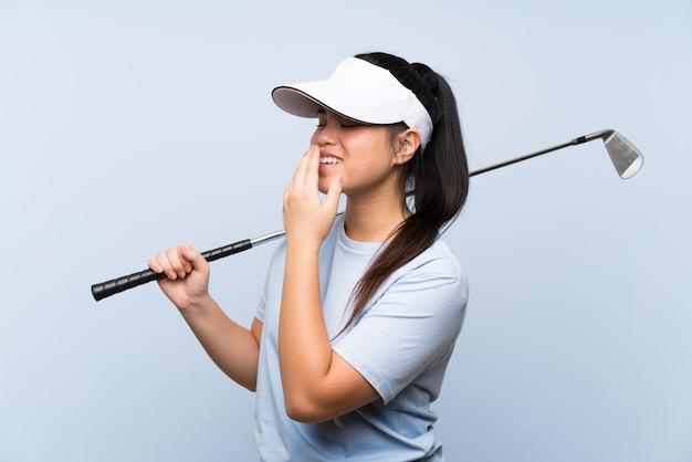 Menina asiática do jogador de golfe novo sobre a parede azul isolada que sorri muito