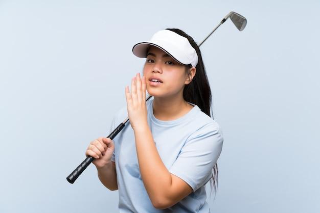Menina asiática do jogador de golfe novo sobre a parede azul isolada que sussurra algo