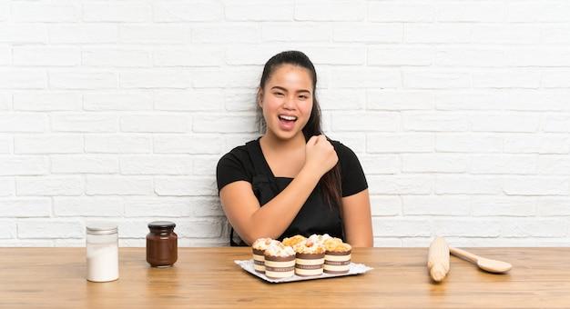 Menina asiática do jovem adolescente com lotes de bolo queque comemorando uma vitória
