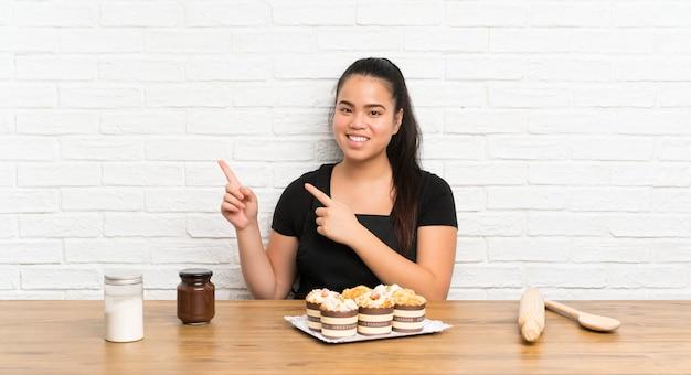 Menina asiática do jovem adolescente com lotes do bolo do queque que aponta o dedo ao lado