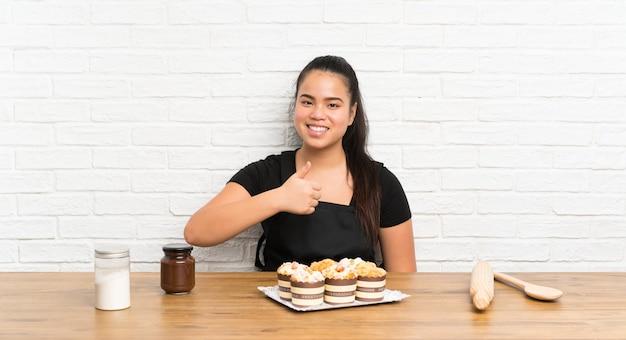 Menina asiática do jovem adolescente com lotes do bolo do queque que dá um polegar para cima gesto