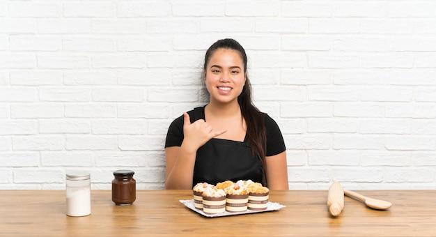 Menina asiática do jovem adolescente com lotes do bolo do queque que faz o gesto do telefone