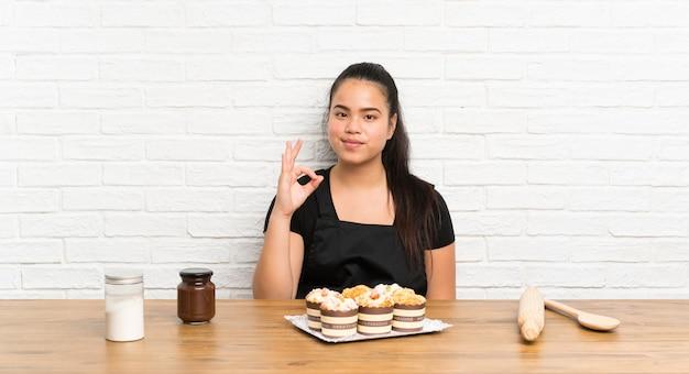 Menina asiática do jovem adolescente com lotes do bolo queque mostrando um sinal de ok com os dedos