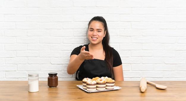 Menina asiática do jovem adolescente com muitos aperto de mão do bolo do queque após o bom negócio