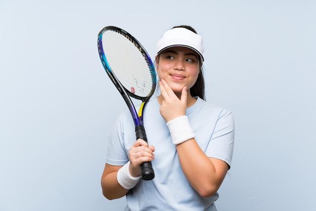 Menina asiática do jovem adolescente que joga o tênis que pensa uma ideia