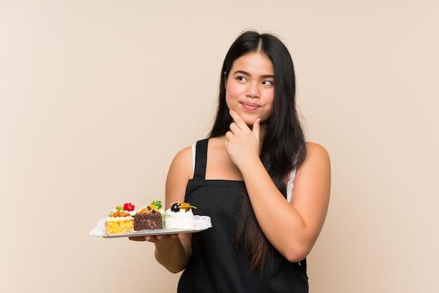 Menina asiática do jovem adolescente que prende muitos mini bolos diferentes sobre a parede isolada que pensa uma ideia