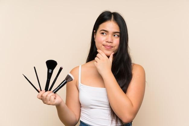 Menina asiática do jovem adolescente segurando um monte de pincel de maquiagem, pensando em uma idéia
