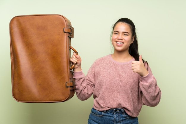 Menina asiática do jovem adolescente sobre fundo verde isolado, segurando uma maleta vintage