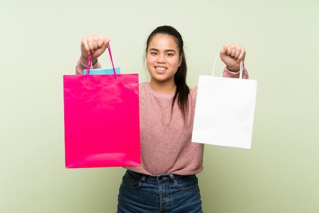Menina asiática do jovem adolescente sobre parede verde isolada, segurando um monte de sacolas de compras
