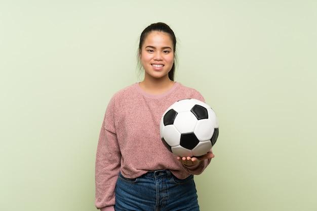 Menina asiática do jovem adolescente sobre parede verde isolada, segurando uma bola de futebol