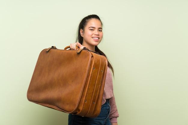 Menina asiática do jovem adolescente sobre parede verde isolada, segurando uma maleta vintage